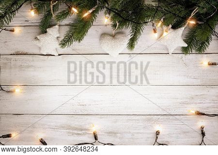 Christmas Lights Bulb And Pine Leaves Decoration On White Wood Plank, Frame Border Design. Merry Chr
