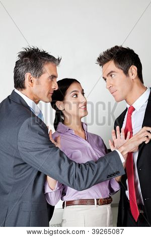 Young woman acting as peacemaker between two fighting business colleagues
