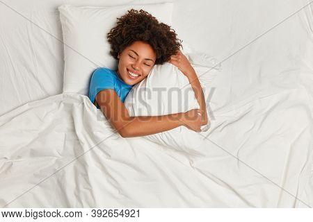 Pleased Dark Skinned Woman Enjoys Nice Dreams During Sleeping, Embraces Pillow, Lies In Bed Comforta
