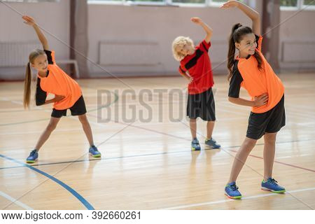 Three Kids Bending To The Right While Exercising In The Gym