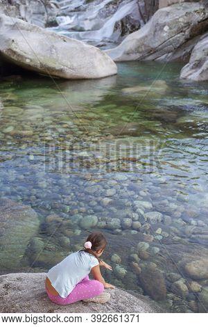 Little Girl Sitting At Riverside Of Los Pilones Gorge At Natural Reserve Garganta De Los Infiernos.