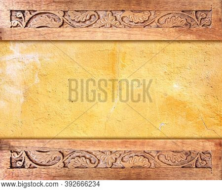 Horizontal background with stucco wall texture, wood frame and carving floral ornament. Decorative carved border on wooden surface. Mock up template. Copy space for text