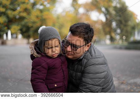 Father Comforting Toddler Child, Parent Support. Autumn, Yellow Leaves. Outdoors Kids Activity