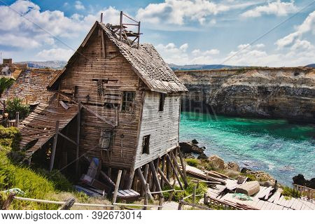Old Abandoned House On The Edge Of A Cliff Overlooking The Sea And Cliffs In The Background