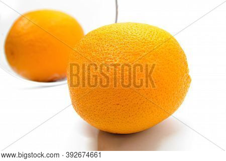 Orange With Thick Peel In Cosmetic Mirror On White Background. Metaphor Of Cellulite Treatment. Skin