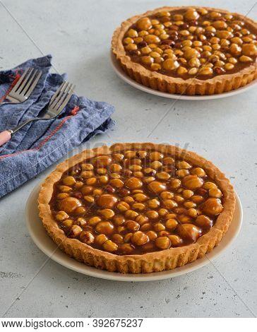 Pie With Hazelnuts And Macadamia Nuts. Nut Tart With Caramel.