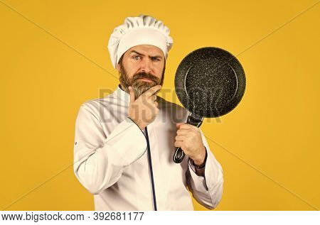 Commercial Kitchen. Cooking Tasty Dish. Bearded Man Hold Frying Pan. Cooking In Pot. For Preparing F