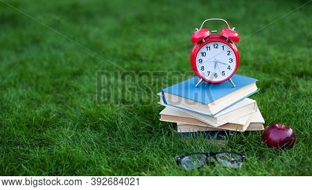 Red Alarm Clock And Stack Old Book In Park In Autumn Morning, Concept Of Education And Reading. Book