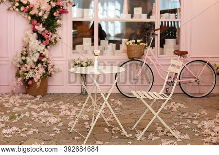 Empty Cafe Terrace With White Table And Chair. Pink Exterior Of The Cafe Restaurant. Interior Street