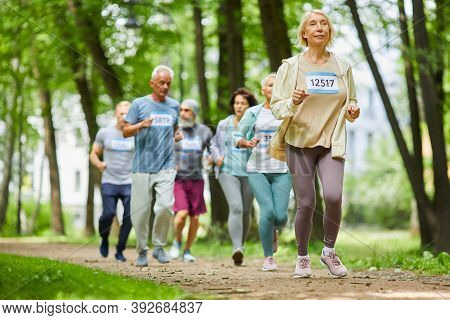 Group Of Modern Active Senior Men And Women Spending Day Time Together In Park Running Marathon, Wid