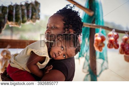 african street vendor, mother holding her child between the bags of peppers and tomatoes in the shed