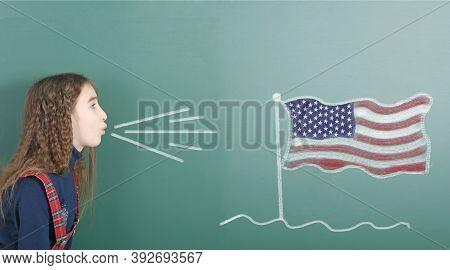 Pre-adolescent Girl Blowing On The School Board Drawn On The Blackboard American Flag. High Resoluti