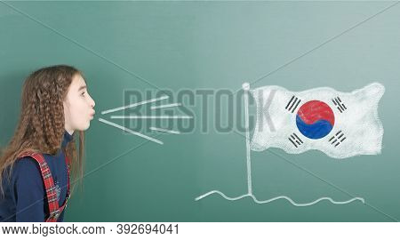 Pre-adolescent Girl Blowing On The School Board Drawn On The Blackboard South Korea Flag. High Resol