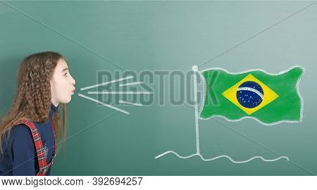 Pre-adolescent Girl Blowing On The School Board Drawn On The Blackboard Brazil Flag. High Resolution