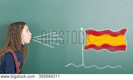 Pre-adolescent Girl Blowing On The School Board Drawn On The Blackboard Spain Flag. High Resolution