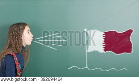 Pre-adolescent Girl Blowing On The School Board Drawn On The Blackboard Qatar Flag. High Resolution
