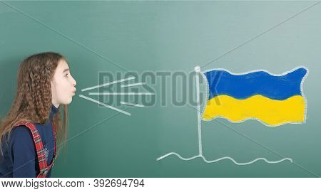 Pre-adolescent Girl Blowing On The School Board Drawn On The Blackboard Ukraine Flag. High Resolutio