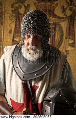 Authentic knight in medieval crusader outfit with helmet, chainmail and sword