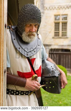 Outdoor pose of a man dressed in authentic Knight Templar outfit or crusader costume standing against a background of a medieval French castle