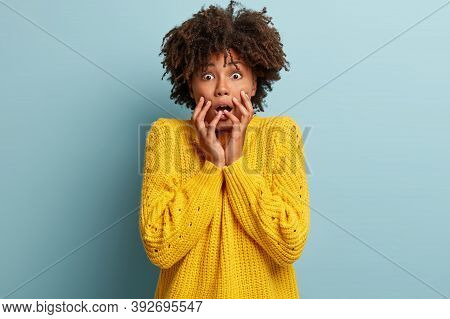 Emotional Scared Afro American Lady Stares With Bated Breath, Feels Intense, Holds Hands Near Face,