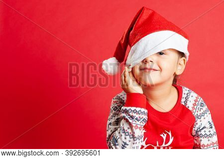 A Smiling Child In Christmas Pajamas, Pulls A Santa Claus Cap Over One Eye, Copy Space On A Red Isol