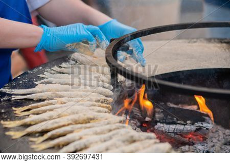 Chef Hand Cooking European Smelt Fish In Flour On Black Brazier At Summer Outdoor Food Market: Close