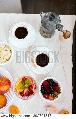 Two Coffee Cups And Italian Coffee Maker With Croissant And Fruits