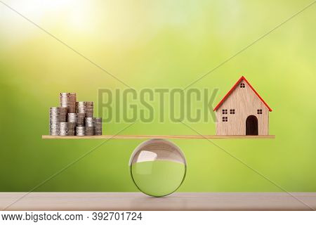 Model House On Wooden Marble Seesaw Balancing With Stacking Coins Money On Green Background. Propert