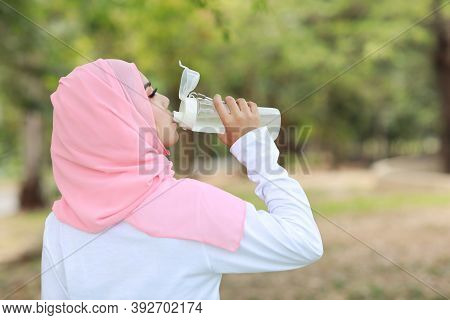 Rear View Fitness Athlete Asian Muslim Woman Drinking Water After Work Out Exercising. Young Cute Gi