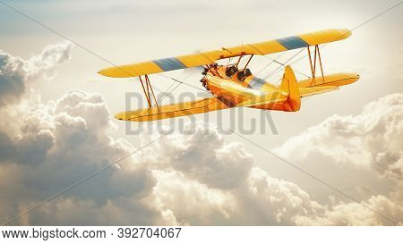 Historical Biplane Into A Dramatic Cloudy Sky