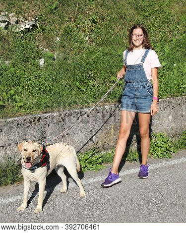 Cute Young Girl  In Dungarees Walking The Dog On A Leash