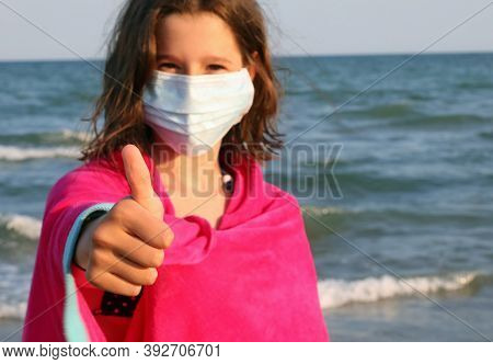 Cute Girl With Surgical Mask Is Ok Keeping The Thumb Lifted By The Sea In Summer