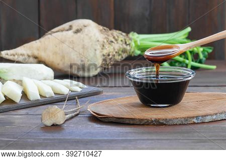 Sugar Beet Molasses In Glass Bowl With Fresh Sugar Beetroot Plant, Healthy Food, Beta Vulgaris