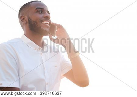 Young successful African broker or agent in white shirt holding smartphone by ear while calling clients and consulting them in front of camera