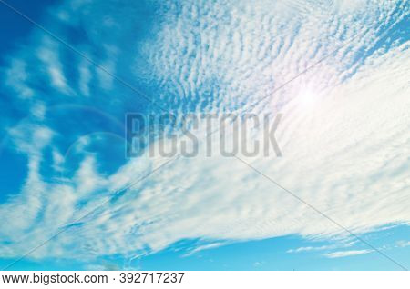 Blue sky background, white dramatic sky fluffy clouds lit by sunset light. Blue sky background, vast sky landscape, sky scene with dramatic clouds. Sky landscape, vast sky view