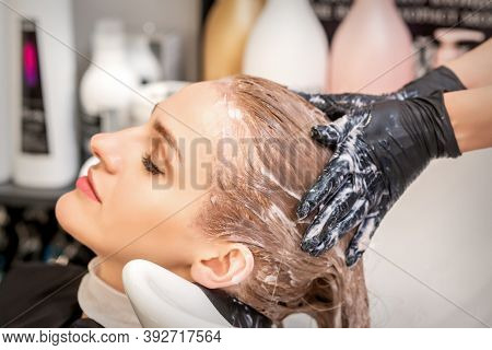Side View Close Up Of Beautiful Young Caucasian Woman Receiving Hair Wash By Hands Of Hairstylist In