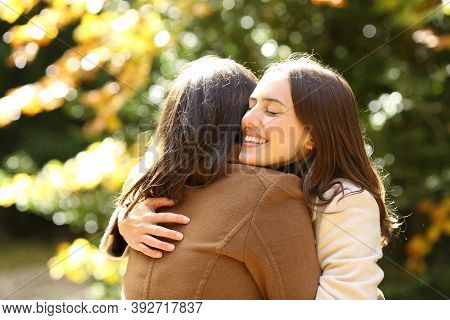 Happy Friends Meeting And Hugging In A Park In Autumn Season A Sunny Day