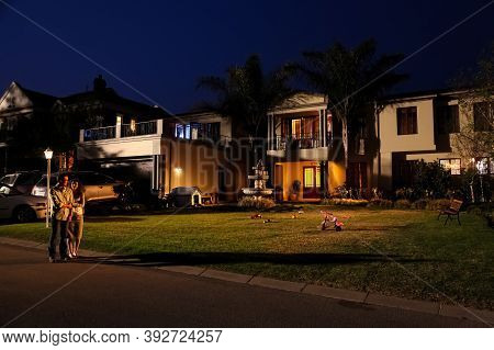 A Couple Walking On The Street Of A Upmarket Wealthy Suburban Neighborhood In Gated Community Estate