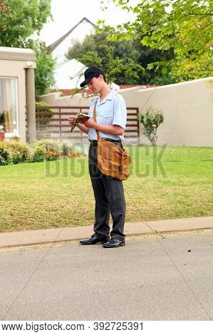 Postal Mailman Hand Delivering Mail In A Wealthy Suburban Neighborhood