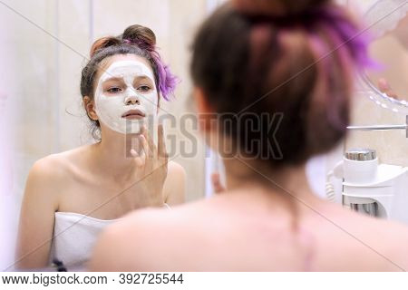 Young Beautiful Woman With White Cosmetic Natural Healing Mask On Face In Bathroom. Cosmetology, Moi