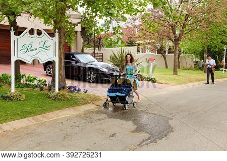 Mom With Pram And Mailman Delivering Mail In A Wealthy Suburban Neighborhood Street