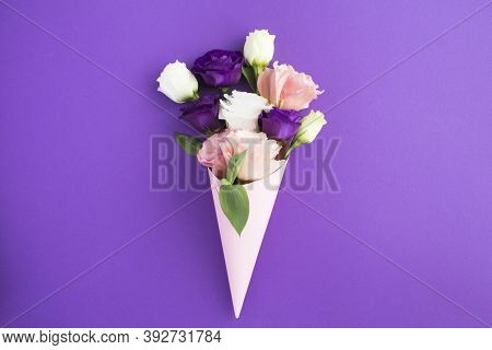White, Pink And Violet Flowers In A Paper Pink Cone On The Violet Background
