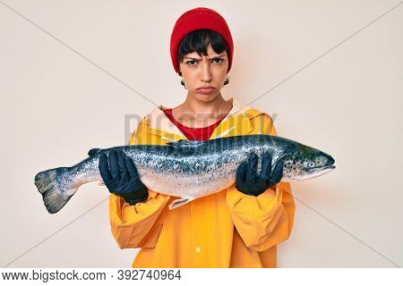 Beautiful brunettte fisher woman wearing raincoat holding fresh salmon skeptic and nervous, frowning upset because of problem. negative person.