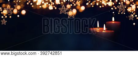 Burning Candles In Christmas Night With Golden Stars And Bokeh For A Background Concept. Space For Y