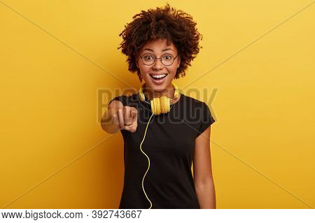 Cute Positive Dark Skinned Girl Wears Balck T Shirt, Round Glasses, Has Yellow Headpohones Connected