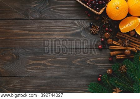 Christmas Spices And Ingredients For Holiday Cooking And Drinks On Dark Wooden Background. Flat Lay,