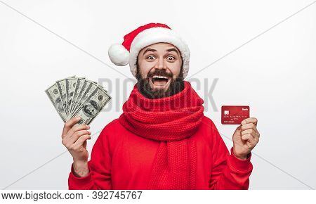 Amazed Bearded Male In Red Sweater And Santa Hat With Scarf Showing Credit Card And Wad Of Money Whi