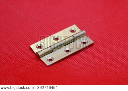 Brass Hinge Without Screws Against Plain Red Background With Copyspace