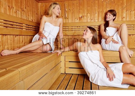 Three attractive women in sauna relaxing and talking