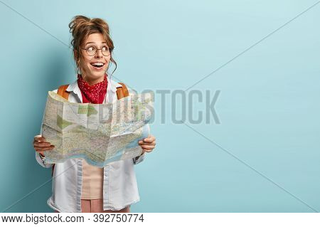 Cheerful European Woman Has Interesting Trip, Looks Aside, Holds Map, Checks Route Or Location, Trav